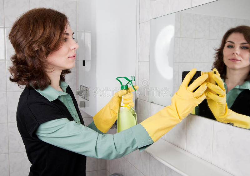 Vrouw die de badkamers schoonmaakt stock afbeelding