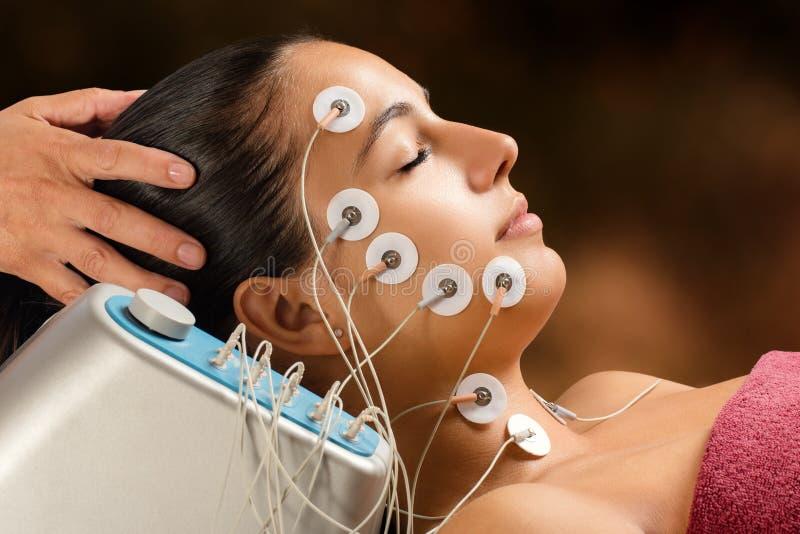 Vrouw die de behandeling van de gezichtslift met elektroden met lage frekwentie hebben royalty-vrije stock fotografie