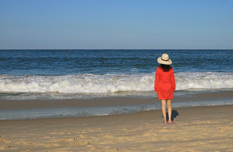 Vrouw die de bespattende golf op het strand bekijken royalty-vrije stock fotografie