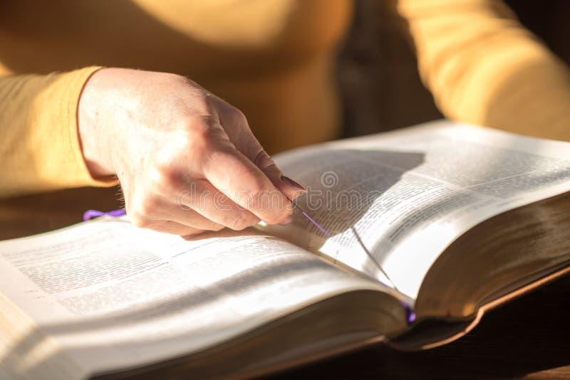 Vrouw die de bijbel, hard licht lezen royalty-vrije stock foto's