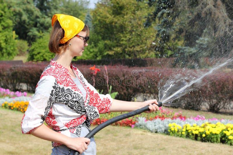 Vrouw die de bloemen water geeft royalty-vrije stock foto's