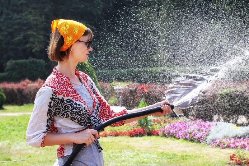 Vrouw die de bloemen water geeft stock afbeeldingen
