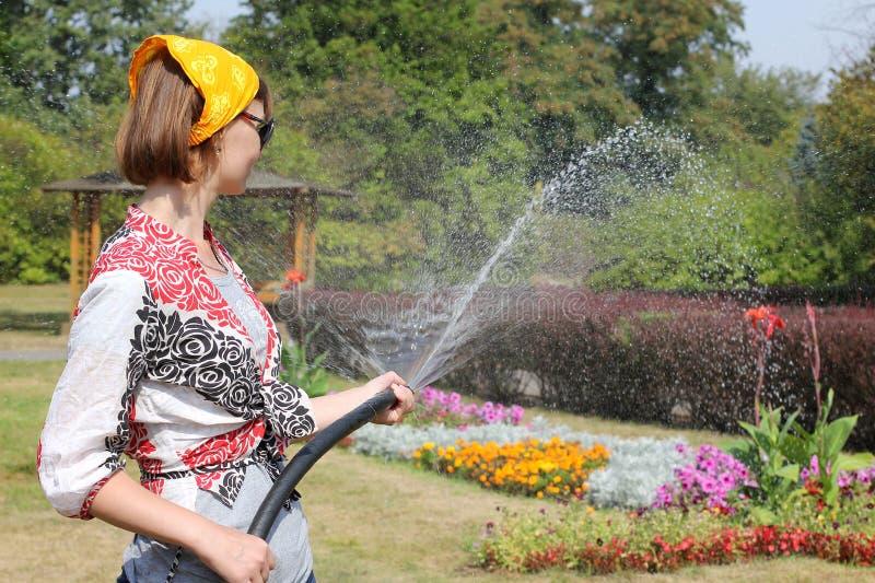 Vrouw die de bloemen water geeft royalty-vrije stock fotografie