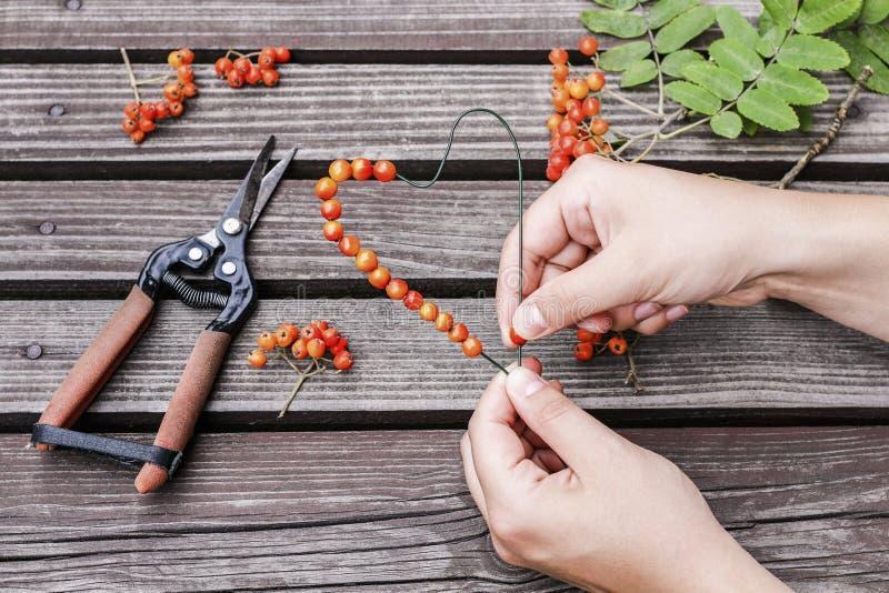 Vrouw die de decoratie van de hartvorm met lijsterbessenbes maken royalty-vrije stock foto's