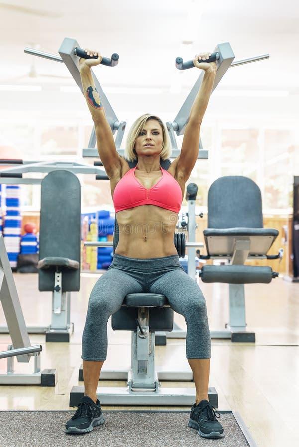 Vrouw die in de gymnastiek uitwerken stock foto