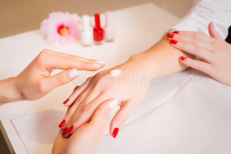 Vrouw die de handen van de vrouw na manicure masseren stock foto's