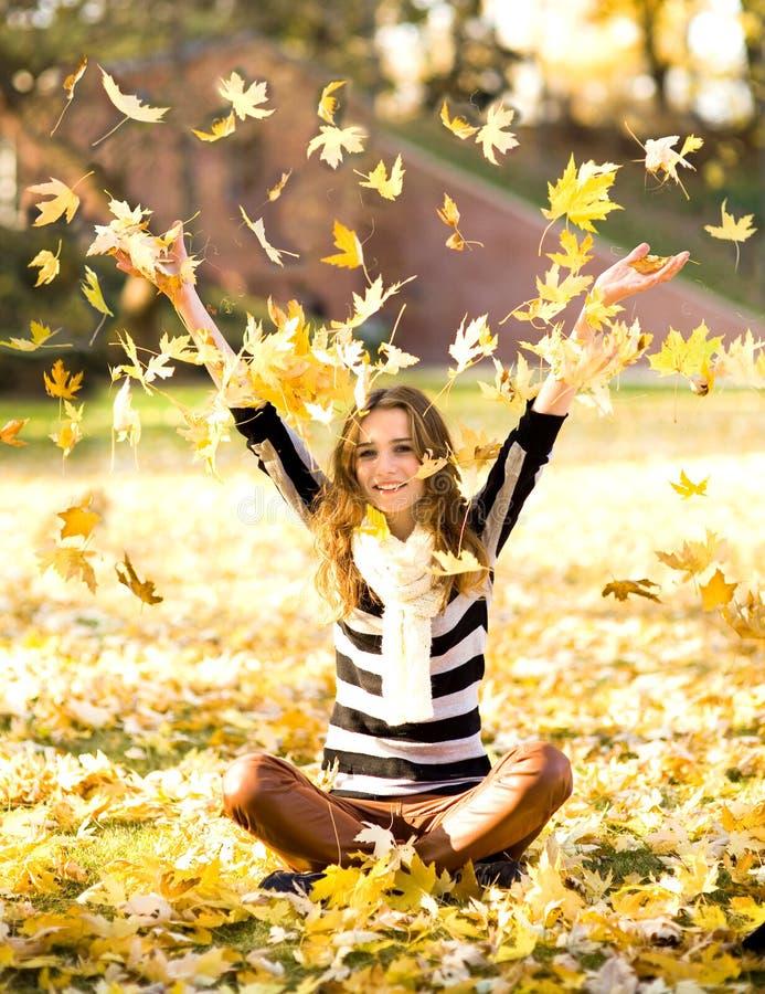 Vrouw die de herfstbladeren werpt royalty-vrije stock foto's