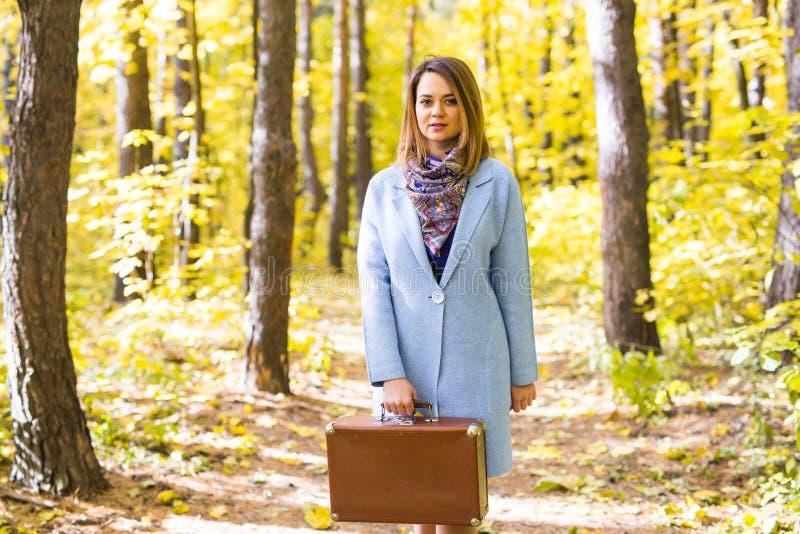 Vrouw die in de herfstpark met koffer lopen stock foto's