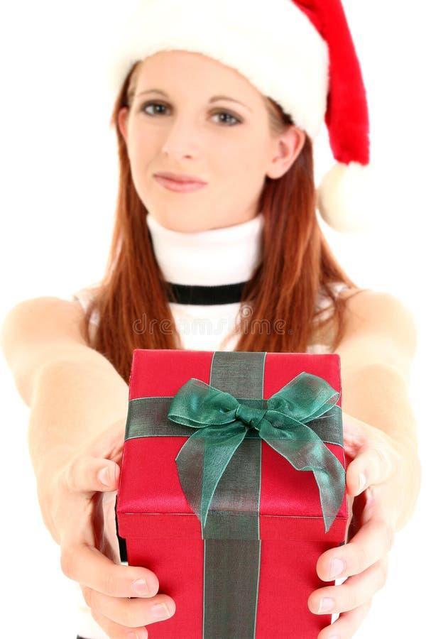 Vrouw die in de Hoed van de Kerstman Gift uitdeelt stock foto's