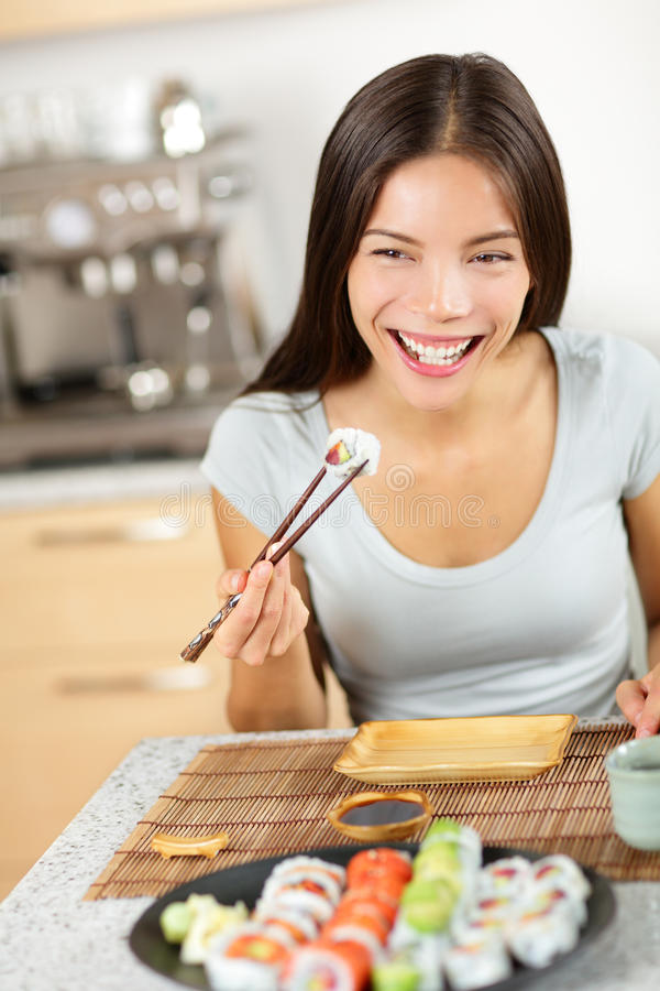 Vrouw die de holdingseetstokjes eten van sushimaki royalty-vrije stock afbeeldingen