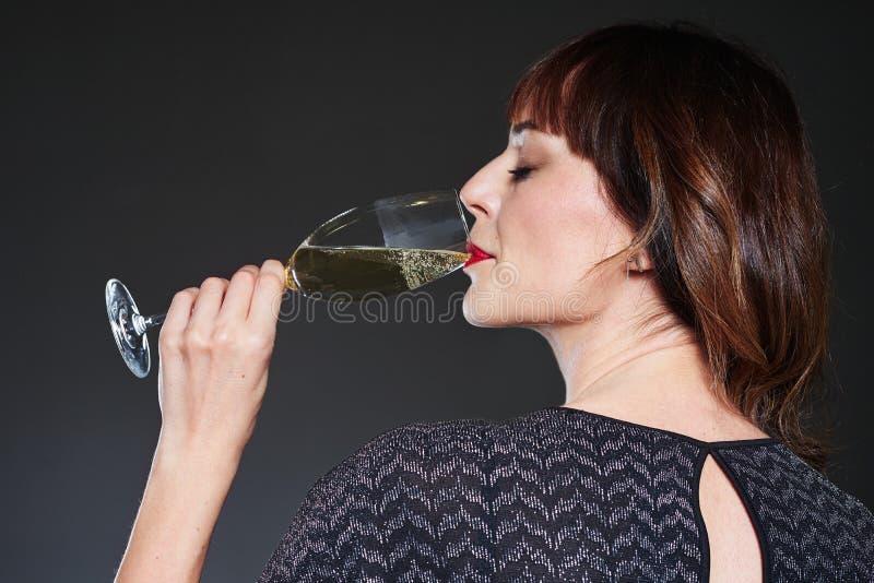Vrouw die de kleding van de nachtpartij het drinken glas champagne op donkere achtergrond dragen Dame met lang krullend haar van  stock afbeelding