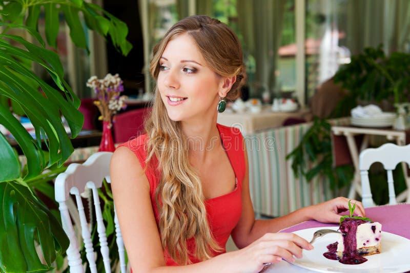 Vrouw die in de koffie rust en cake eet royalty-vrije stock foto's