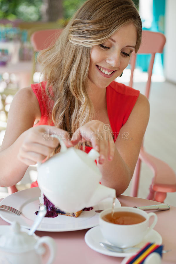 Vrouw die de kop thee giet stock afbeeldingen