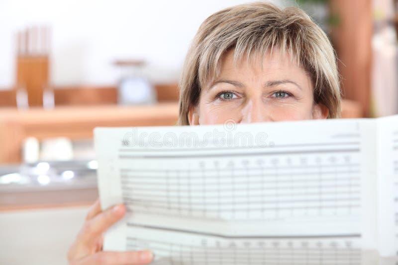 Vrouw die de krant leest stock fotografie