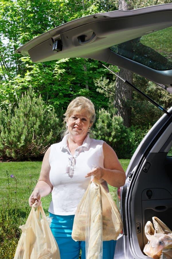 Vrouw die de kruidenierswinkels leegmaakt stock foto's
