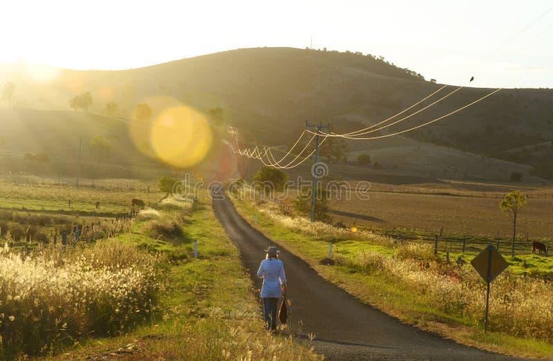Vrouw die de lange zonsondergang van het landweghuis lopen stock foto's