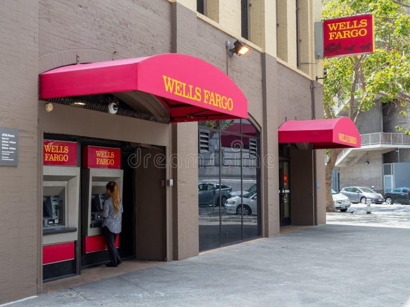 Vrouw die de machine van Wells Fargo ATM buiten takplaats met behulp van royalty-vrije stock foto