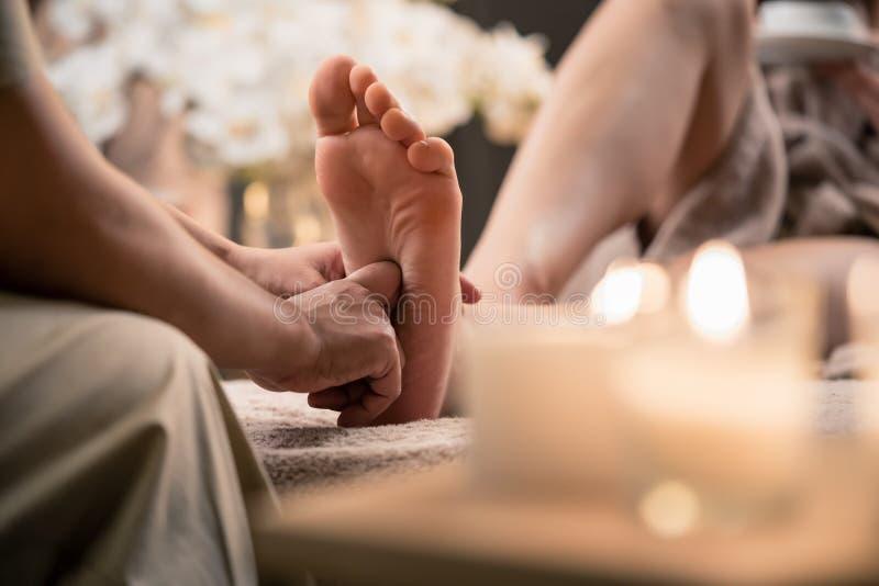 Vrouw die de massage van de reflexologyvoet in wellness spa hebben stock afbeelding