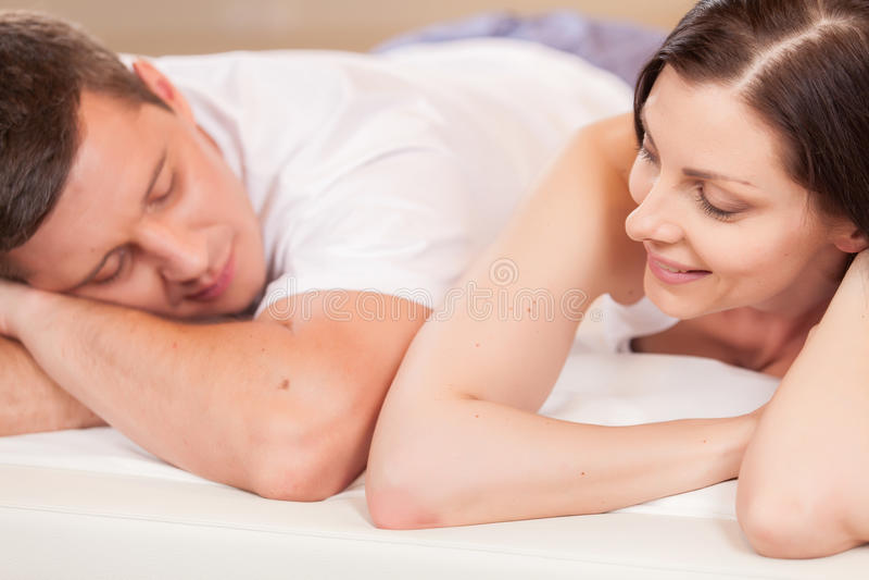 Vrouw die de mens bekijken en in bed liggen stock afbeeldingen