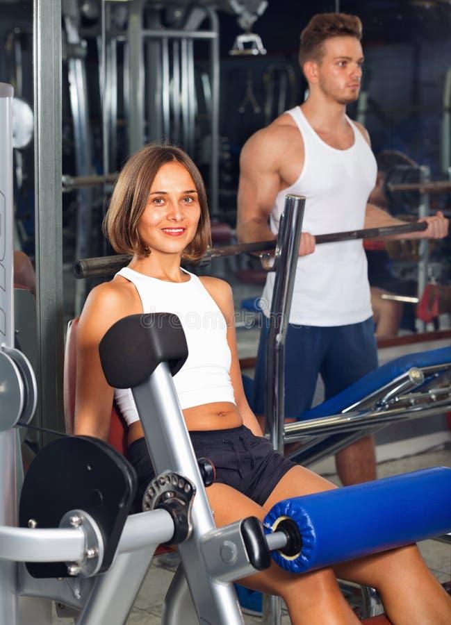 Vrouw die de oefening maken die van de beenuitbreiding gymnastiekmachines met behulp van royalty-vrije stock foto's