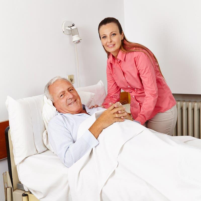 Vrouw die de oude mens in het ziekenhuis bezoeken royalty-vrije stock afbeeldingen