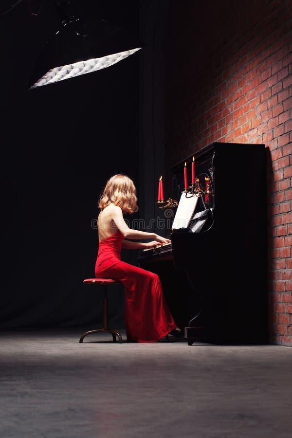 Vrouw die de piano speelt stock afbeelding