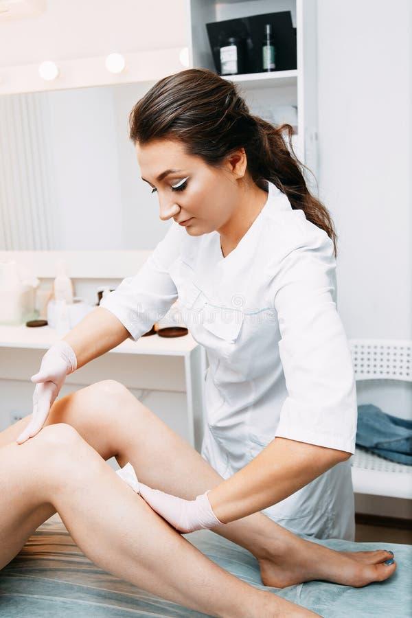 Vrouw die de procedure van de haarverwijdering aangaande benen in salon hebben stock fotografie