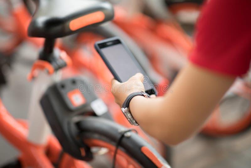 Vrouw die de QR-code van gedeelde fiets aftasten stock fotografie
