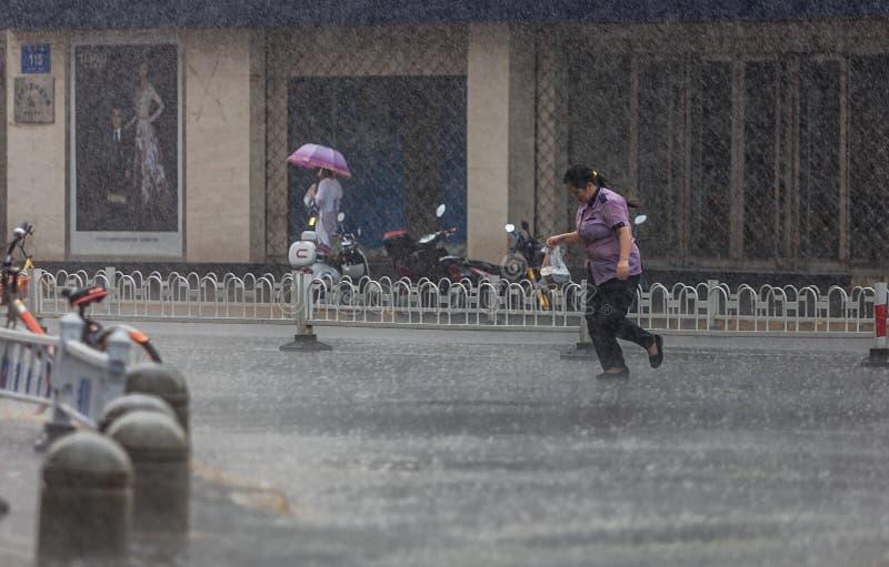 Vrouw die in de regen lopen stock afbeelding