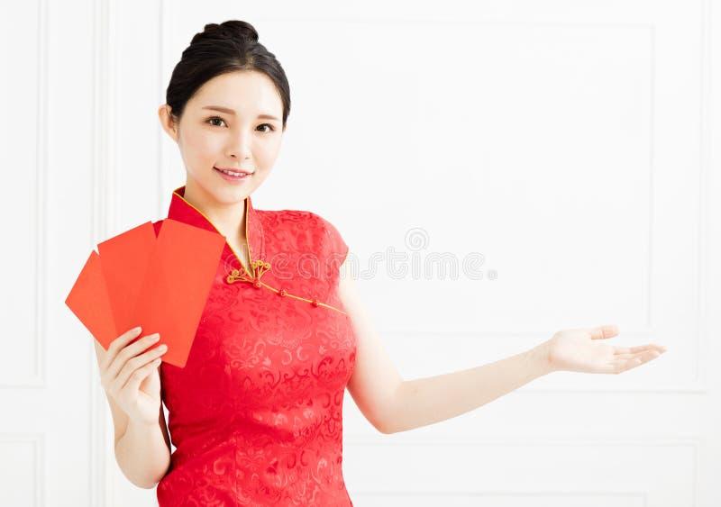 vrouw die de rode envelop tonen en iets introduceren stock afbeeldingen