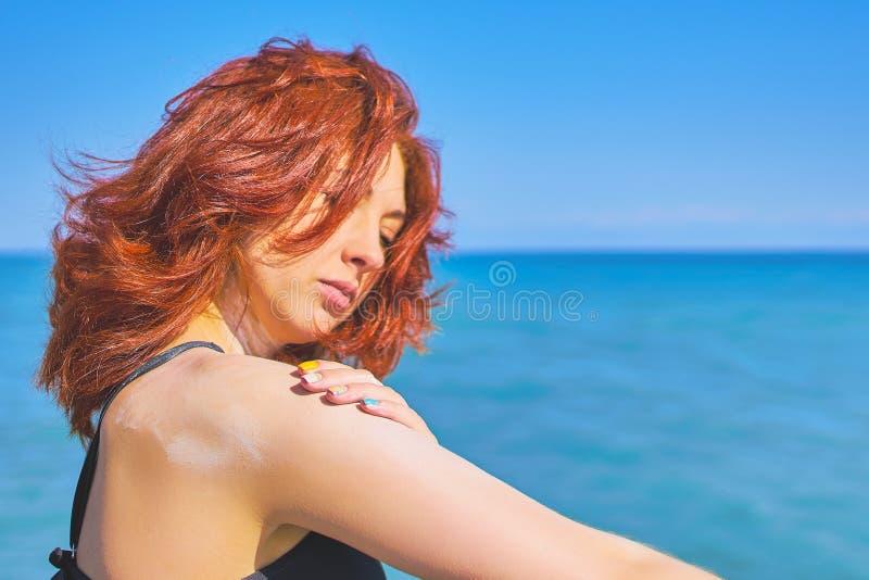 Vrouw die de room van de zonbescherming toepast stock afbeelding