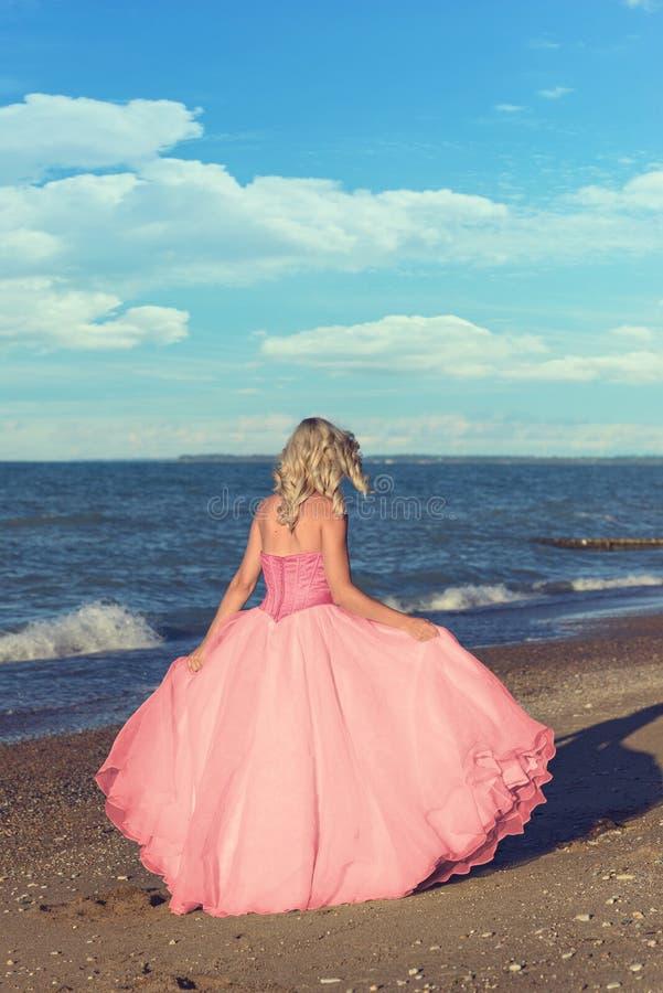 Vrouw die in de roze kleding van Tulle op het strand lopen stock afbeeldingen
