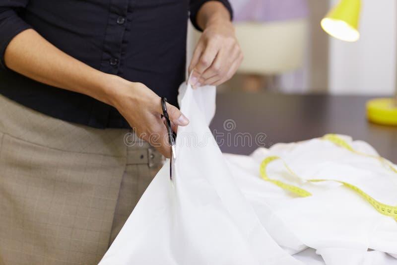 Vrouw die in de studio van het manierontwerp werkt stock foto's
