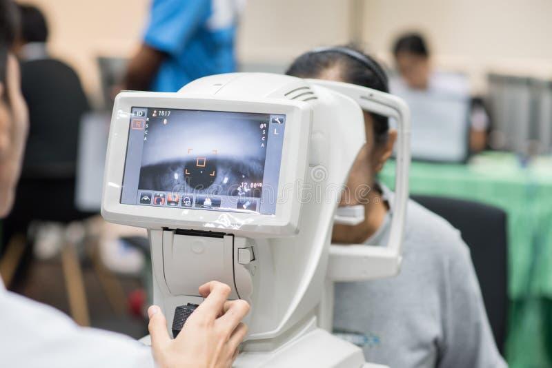Vrouw die de testmachine van het refractometeroog bekijken in oftalmologie stock afbeelding