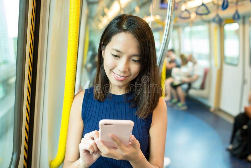 Vrouw die de treincompartiment gebruiken van de cellphonebinnenkant royalty-vrije stock fotografie
