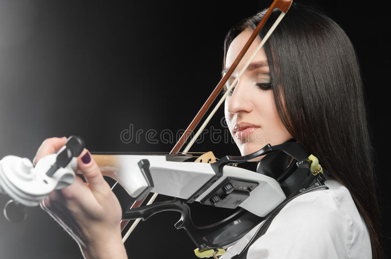 Vrouw die de viool op een zwarte achtergrond spelen royalty-vrije stock afbeeldingen