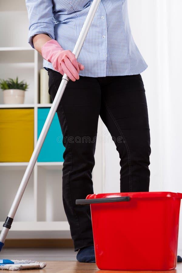 Vrouw die de vloer afvegen stock foto