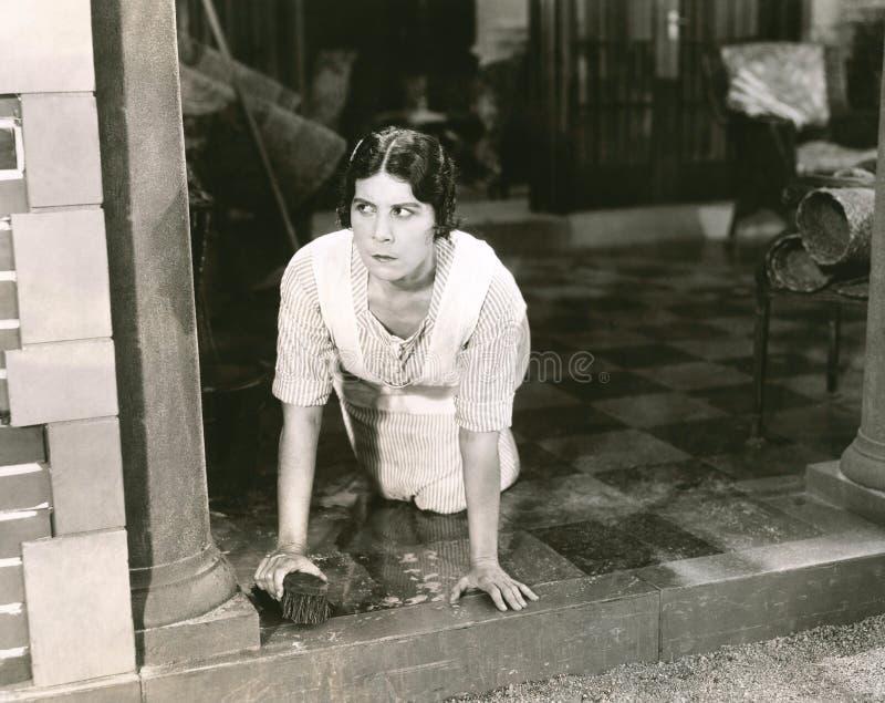 Vrouw die de vloer schrobben stock foto's