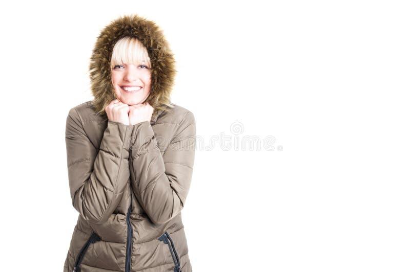 Vrouw die de winterjasje met koud en kap dragen die zijn glimlachen royalty-vrije stock afbeelding
