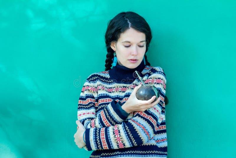 Vrouw die de wollen sweater van het sneeuwvlokkenpatroon en turkooise oorringen dragen die hete yerbapartner drinken stock afbeeldingen