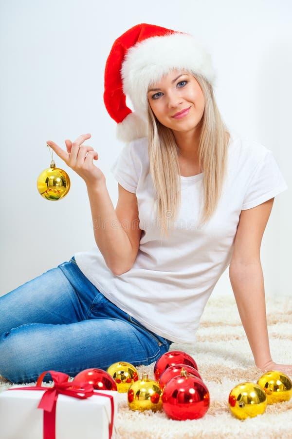 Vrouw die de zitting van de santahoed op de vloer draagt royalty-vrije stock foto's