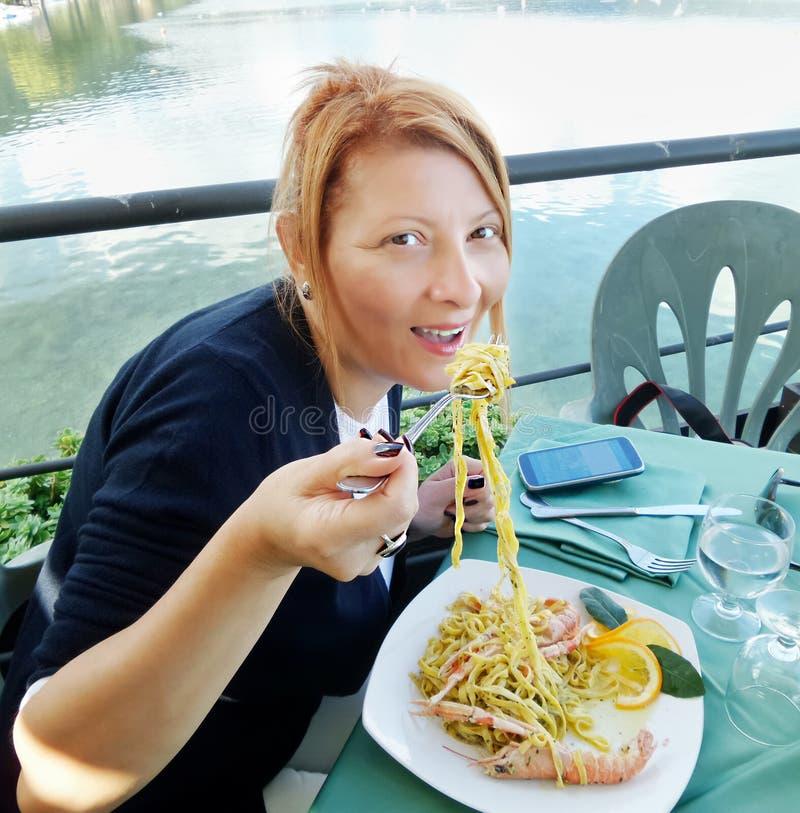 Vrouw die Deegwaren eet stock afbeeldingen