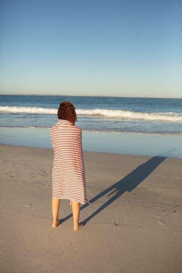 Vrouw die in deken wordt verpakt die zich op strand in de zonneschijn bevinden stock afbeeldingen