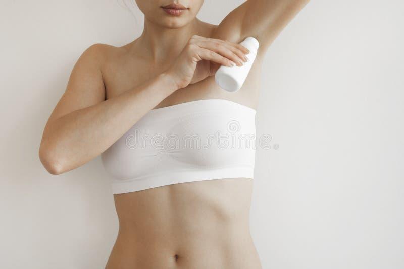 Vrouw die deodorant op haar oksel toepassen royalty-vrije stock afbeeldingen