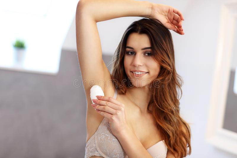 Vrouw die deodorant op oksel in badkamers toepassen stock afbeelding