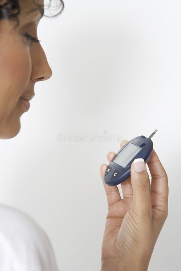 Vrouw die Diabetes controleren die Glucometer gebruiken royalty-vrije stock foto