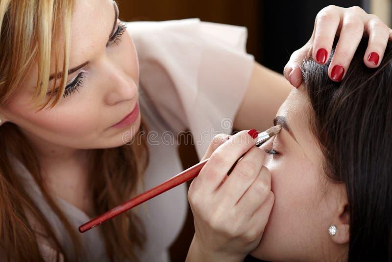 Vrouw die die make-up hebben door make-upkunstenaar wordt toegepast royalty-vrije stock foto