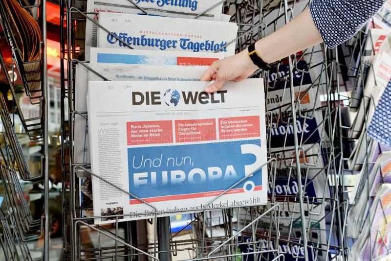 Vrouw die Die Welt-krant met het schokken van krantekop over Br kopen stock afbeelding