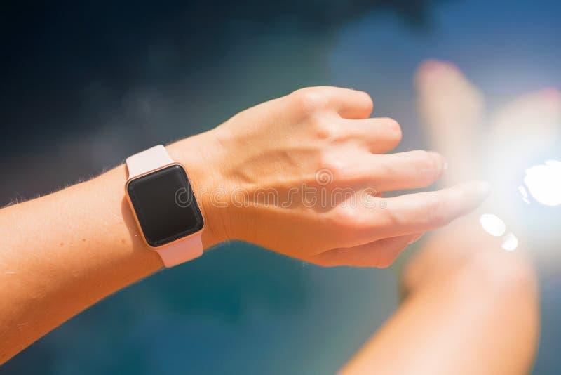 Vrouw die digitaal horloge op hand dragen door de pool royalty-vrije stock foto