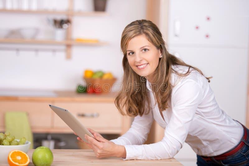 Vrouw die digitaal stootkussen in de keuken gebruiken royalty-vrije stock afbeeldingen